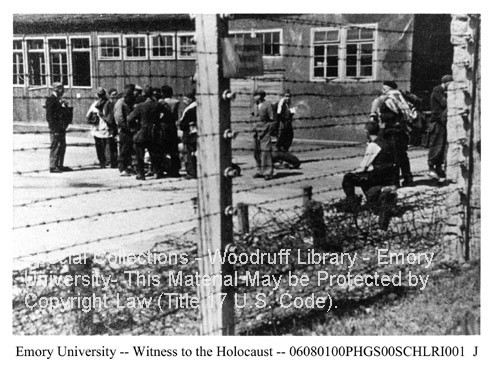 Photo of concentration camp taken through barbed wire fence