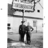 """Two liberators stand under a sign reading """"We welcome our liberators"""" at Flossenburg"""