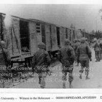 Soldiers walk by open boxcars  [Dachau]
