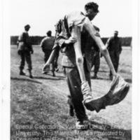A German civilian carrying the corpse of a prisoner over his shoulder (2) [Landsberg]