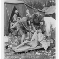 Liberators tend to survivors of Ebensee near the tents of the 30th Field Hospital