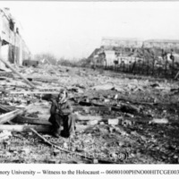 A male survivor with a bandage around his head sits on debris in front of building ruins [Nordhausen]