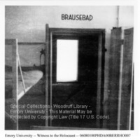 """""""BRAUSEBAD"""" (showers) painted over the doorway of a room with bunk beds in it  [Dachau]"""